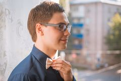 Portrait of young groom tying bow tie while getting ready for wedding Stock Photography