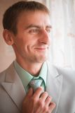 Portrait of young groom tying tie while getting ready for wedding Royalty Free Stock Images