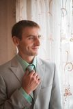 Portrait of young groom tying tie while getting ready for wedding Stock Photo