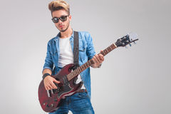 Portrait of young guitarist playing guitar in studio Royalty Free Stock Photography