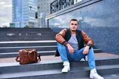 Portrait of young guy alone in leather jacket sitting on the stairs in the city stock image