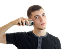 Portrait of a young guy in a black t-shirt who shaves with a severe face close-up Royalty Free Stock Images