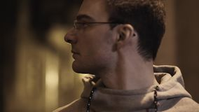 Portrait of young guy in glasses out of breath turns around in alleyway. Portrait of young cauasian unshaved guy in glasses and gray hoodie out of breath turns stock footage