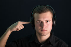 Portrait of young guy with headphones. On the dark background Stock Images