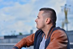 Portrait of young guy in leather jacket against blue sky with clouds stock photo