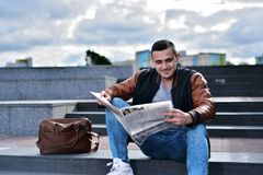 Portrait of young guy in leather jacket with bag smiling and reading newspaper stock image