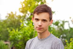 Portrait of a young guy on a natural green background stock photo