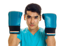 Portrait of young guy practicing boxing in blue gloves isolated on white background Royalty Free Stock Images