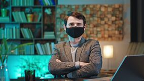 Portrait of a young guy with a protective mask in front of the camera he working on the office and take carefully of the