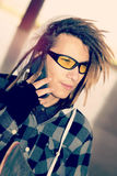 Portrait of young guy  with rasta hair talking phone warm filter Royalty Free Stock Images