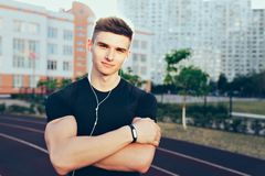 Portrait of young guy with a sport body in the morning on stadium. He wears black T-shirt, headphones. He keeps muscular. Hands crossed and smiles to camera stock photography