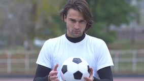 Portrait of a young guy in a sports t-shirt holding a soccer ball in his hands and strictly looking at the camera Sports stock video footage