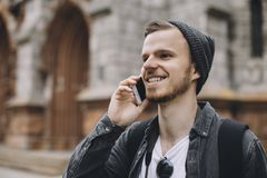 The portrait of a young guy talking on the phone. He is enjoying the conversation and smiling. Aparently this man is waiting for somebody. Close up. Cut view Royalty Free Stock Photo