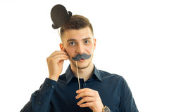 Portrait of a young guy who stands in the Studio and keeps the paper Dummies for photo near face Royalty Free Stock Images