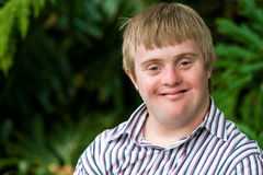 Portrait of young handicapped man. Close up portrait of young handicapped man with green leaves in background Stock Photos