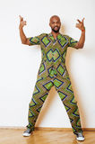 Portrait of young handsome african man wearing bright green national costume smiling gesturing Royalty Free Stock Photos