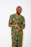 Portrait of young handsome african man wearing bright green national costume smiling gesturing Stock Image