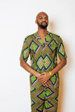 Portrait of young handsome african man wearing bright green national costume smiling gesturing Royalty Free Stock Images
