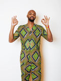Portrait of young handsome african man wearing bright green national costume smiling gesturing Stock Photo