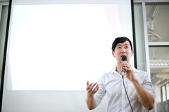 Portrait of young handsome Asian male speaker publicly speaking on stage to group of audience with white board behind. royalty free stock photography