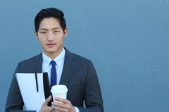 Portrait of a young handsome Asian man businessman in black classic suit with trendy blue tie. Close up of a coffee break. With copy space Stock Photography