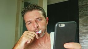 Portrait of young handsome and attractive internet addict man at home bathroom with towel on shoulder washing teeth with royalty free stock images