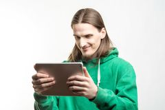 Portrait of young handsome beaded smiling man in green hoodie looking at the digital tablet in his hands agains white background. Lifestyle, people and Stock Image