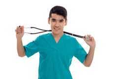 Portrait of young handsome brunette man doctor in blue uniform with stethoscope looking and smiling on camera isolated Royalty Free Stock Images