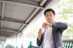 Portrait of young handsome business man drinking coffee looking wrist watch. Royalty Free Stock Image