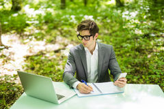 Portrait of young handsome business man in suit working at laptop at office table and talk at phone with costumer and make notice. Portrait of young handsome stock photography