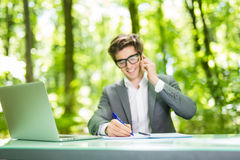 Portrait of young handsome business man working at laptop at office table and talk at phone with costumer and make notice and smil. Portrait of young handsome stock photography