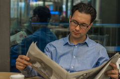 Portrait of a young handsome businessman reading a newspaper at his breakfast in coffee shop Royalty Free Stock Images