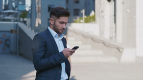 Young Handsome Businessman Standing near Big Office Building. Typing a Message on his Smartphone.Bearded Man Wearing. Portrait of Young Handsome Businessman stock video footage