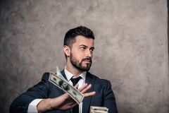 Portrait of a young handsome businessman throwing out money banknotes. wearing suit and a tie stock images