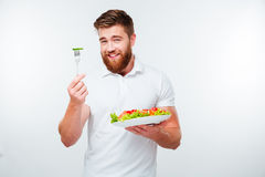 Portrait of a young handsome casual man eating salad Stock Images