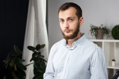 Portrait of a young handsome Caucasian brunette man with a beard. 20-25 years old standing in plaid shirt. Hands folded on his. Chest. Serious emotion on the stock photography