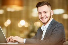Businessman with toothy smile. Portrait of young handsome Caucasian man in business suit sitting at laptop and smiling at camera cheerfully on blurred background Stock Photo