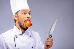 Portrait of young handsome cook. Ready for a culinary sensation. Closeup portrait of handsome funny cook in uniform holding a knife and keeping an apple in his Royalty Free Stock Photos