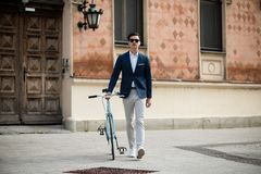 Elegant young man with bicycle. Portrait of a young handsome and elegant man in blue suit with bicycle outdoors, on the street Stock Photos
