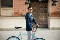 Elegant young man in suit with bicycle. Portrait of a young handsome and elegant man in blue suit with bicycle outdoors, on the street Stock Image