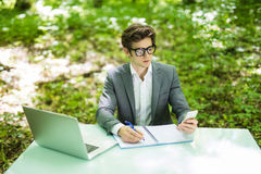 Portrait of young handsome freelance working at laptop at office table and talk at phone with costumer and make notice in green fo. Portrait of young handsome stock photos