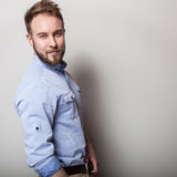 Portrait of young handsome friendly man in blue shirt. Studio photo on light grey background.  Royalty Free Stock Images