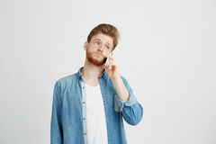 Portrait of young handsome guy with beard speaking on phone over white background. Copy space royalty free stock image