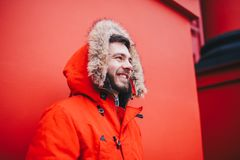 Portrait of a young handsome guy, a student with a beard in a red winter jacket and a hood with fur on the background of the red w. All of the building of an Stock Images