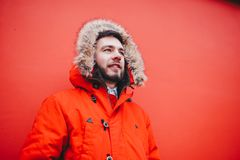 Portrait of a young handsome guy, a student with a beard in a red winter jacket and a hood with fur on the background of the red w. All of the building of an Stock Image