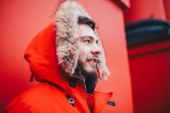 Portrait of a young handsome guy, a student with a beard in a red winter jacket and a hood with fur on the background of the red w. All of the building of an Royalty Free Stock Photo