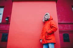 Portrait of a young handsome guy, a student with a beard in a red winter jacket and a hood with fur on the background of the red w. All of the building of an Stock Photos