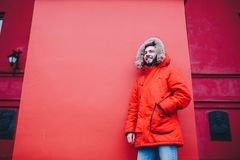 Portrait of a young handsome guy, a student with a beard in a red winter jacket and a hood with fur on the background of the red w. All of the building of an Royalty Free Stock Photos
