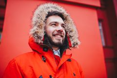 Portrait of a young handsome guy, a student with a beard in a red winter jacket and a hood with fur on the background of the red w. All of the building of an Stock Photography