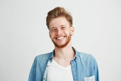 Portrait of young handsome hipster man with beard smiling laughing looking at camera over white background. Royalty Free Stock Photo